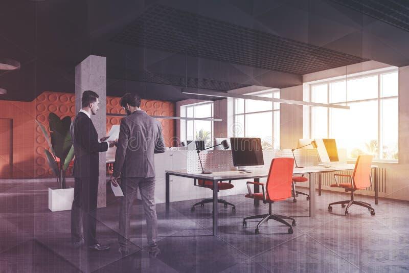 Två affärsmän i orange öppet utrymmekontor royaltyfria foton