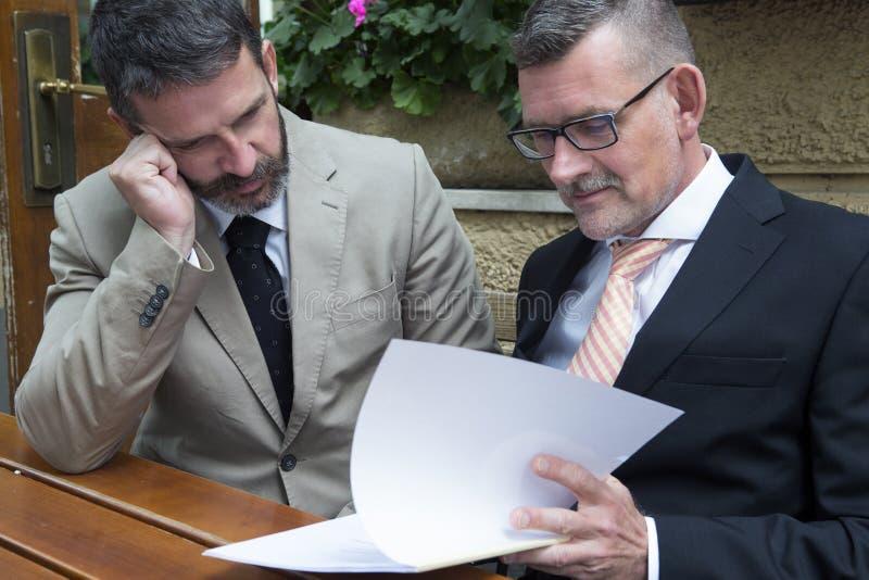 Två affärsmän med skrivbordsarbete på en restaurang royaltyfri foto