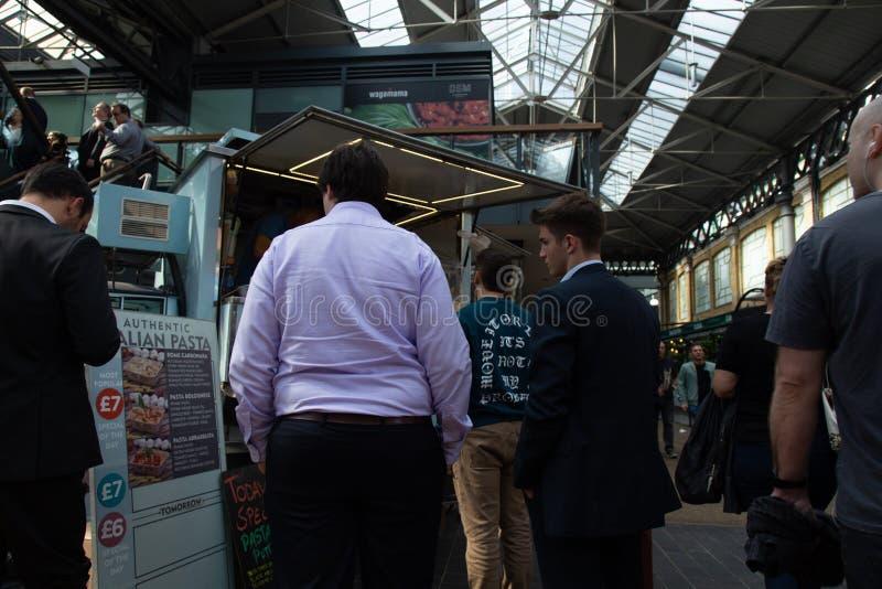 Två affärsmän på gatamatmarknad i den gamla Spitalfields marknaden London arkivbilder