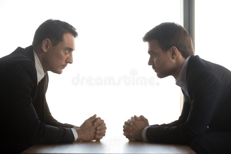 Två affärsmän ser de att sitta som är motsatt, rivalitetbegrepp arkivfoto