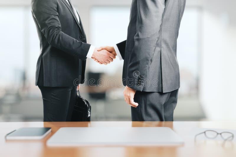 Två affärsmän skakar händer i kontoret royaltyfri fotografi