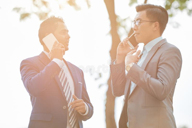 Två affärsmän som är upptagna med påringningar arkivbilder