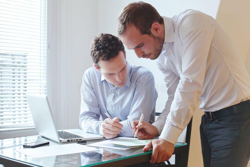 Två affärsmän som arbetar i kontoret royaltyfri fotografi