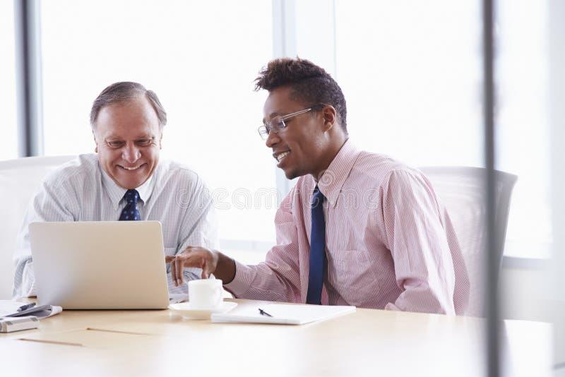 Två affärsmän som arbetar på bärbara datorn på styrelsetabellen royaltyfria foton