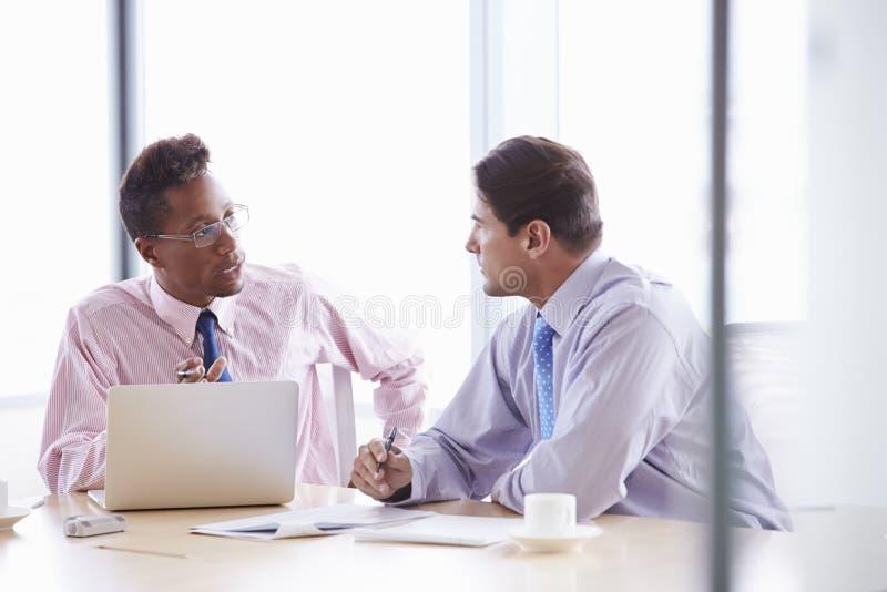 Två affärsmän som arbetar på bärbara datorn på styrelsetabellen royaltyfri fotografi