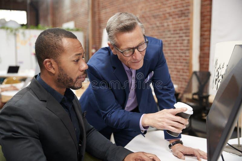 Två affärsmän som arbetar på datoren på skrivbordet i öppet plankontor royaltyfri fotografi