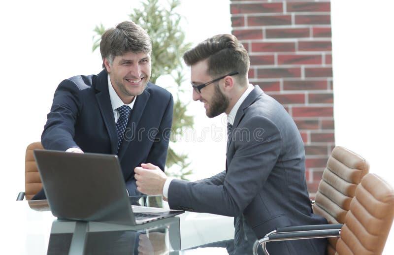 Två affärsmän som arbetar tillsammans genom att använda bärbara datorn på affärsmöte i regeringsställning arkivfoto