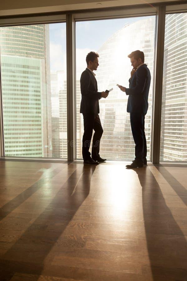 Två affärsmän som delar idéer på kort möte arkivfoto