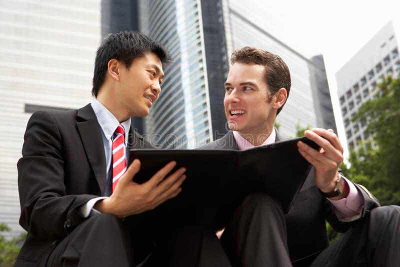 Två affärsmän som diskuterar förlagan utanför kontor royaltyfri bild