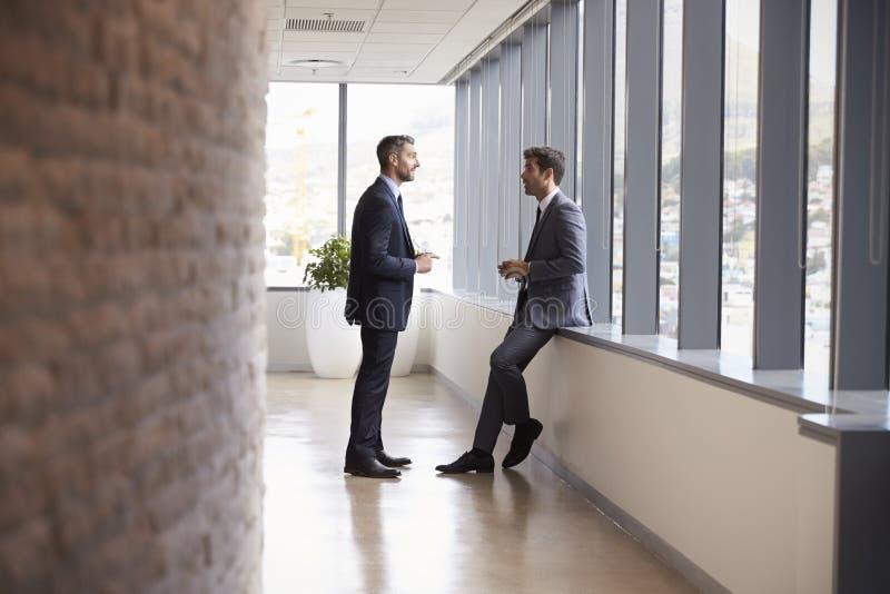 Två affärsmän som har informellt möta i regeringsställning korridoren royaltyfria bilder