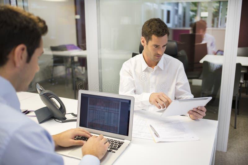 Två affärsmän som i regeringsställning arbetar med bärbar dator- och minnestavlaPC royaltyfria bilder