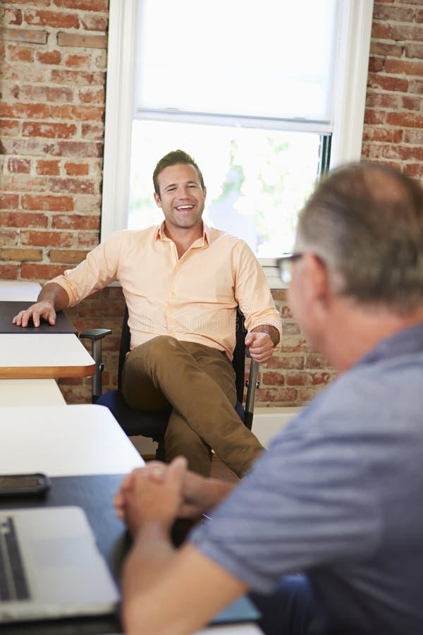 Två affärsmän som möter i idérikt kontor arkivbilder