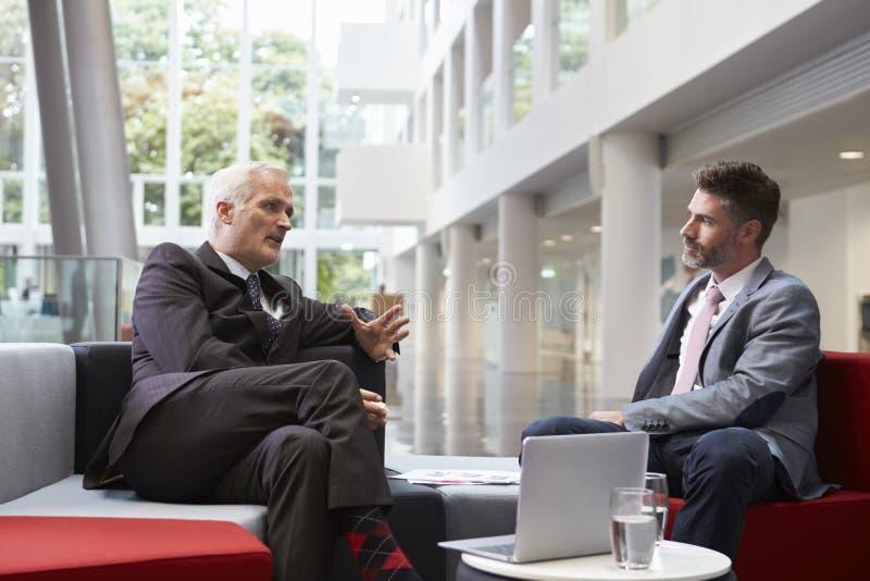 Två affärsmän som möter i lobbyområde av det moderna kontoret arkivfoto