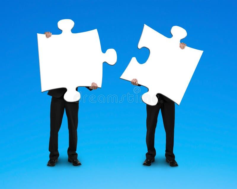 Två affärsmän som monterar pussel arkivbild