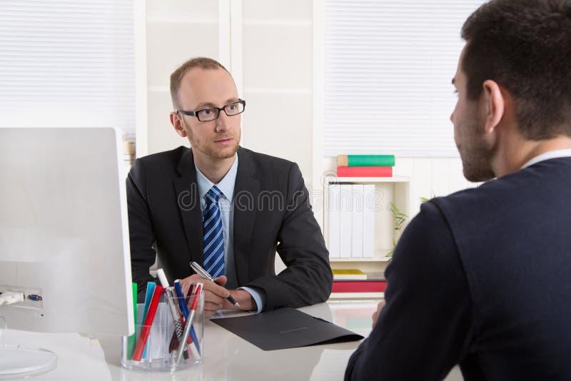 Två affärsmän som sitter i kontoret: möte eller jobbintervju arkivfoto