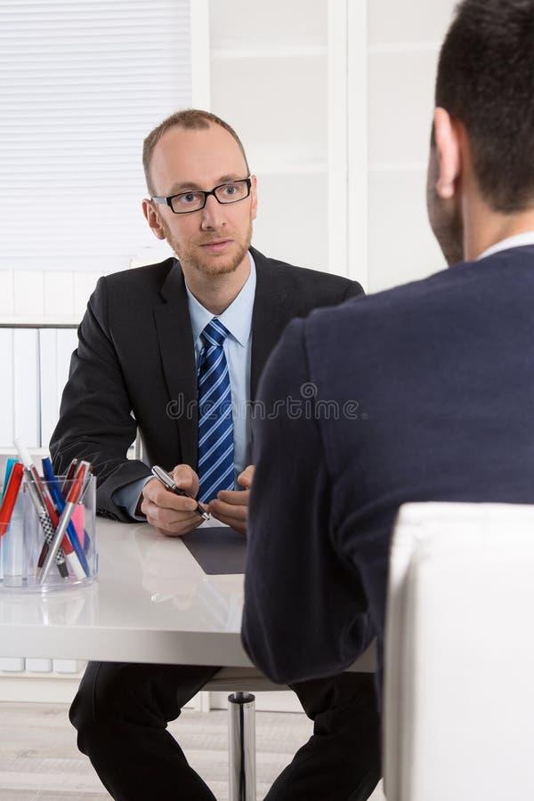 Två affärsmän som sitter i kontoret: möte eller jobbintervju royaltyfri foto