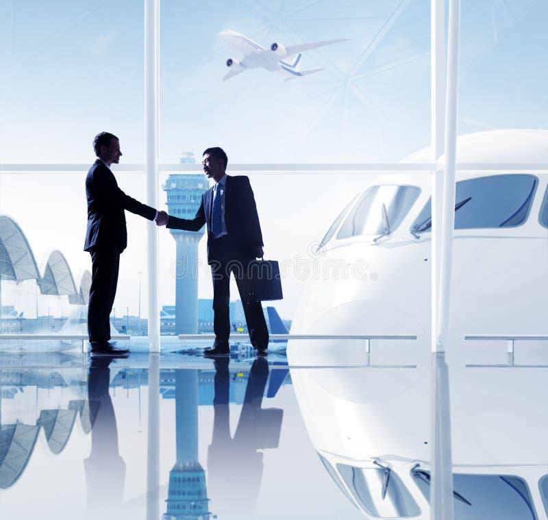Två affärsmän som skakar händer i en flygplats royaltyfria foton
