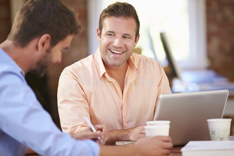 Två affärsmän som tillsammans arbetar på skrivbordet royaltyfri fotografi
