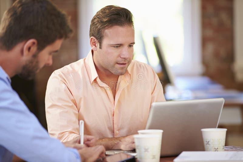 Två affärsmän som tillsammans arbetar på skrivbordet royaltyfri foto