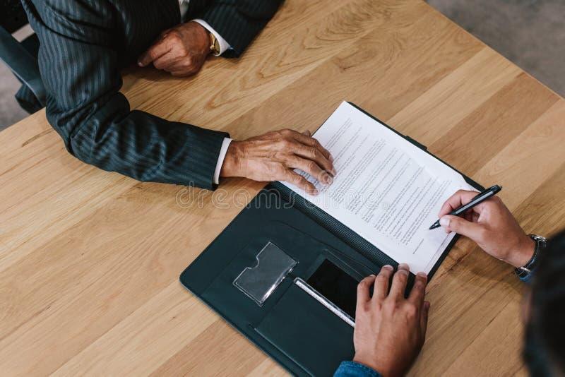 Två affärsmän som undertecknar avtalet royaltyfri bild