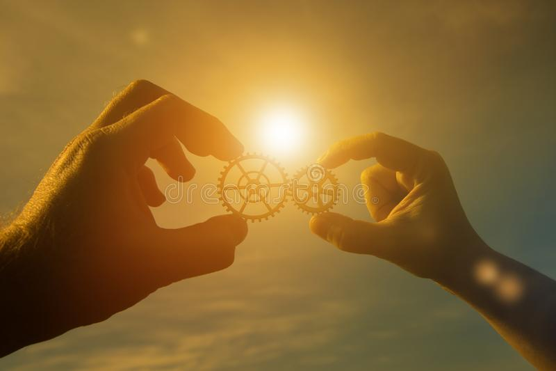 Två affärsmanhänder förbinder detaljerna av ett pussel av kugghjul mot en solnedgångbakgrund royaltyfria foton
