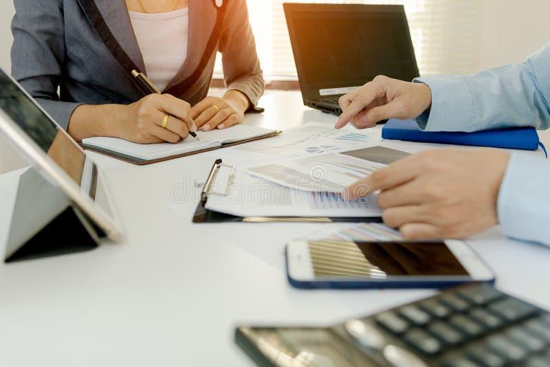 Två affärsmankollegor som diskuterar finansiella grafdata för plan på kontorstabellen med bärbara datorn och den digitala minnest royaltyfri fotografi