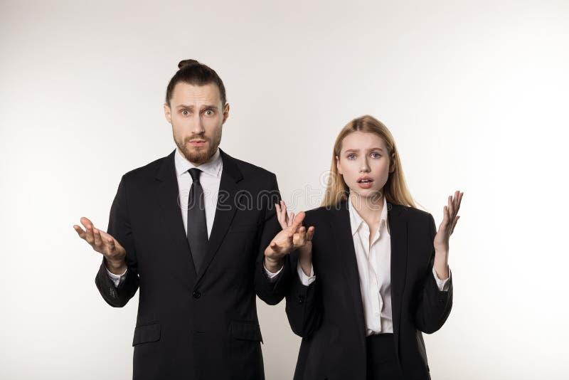Två affärspartners i svarta den chockade dräkter, stilig skäggig man och härliga blonda kvinnan vet inte vad för att göra fotografering för bildbyråer