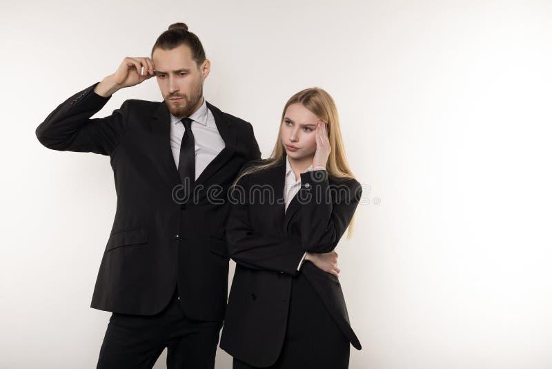Två affärspartners i svarta dräkter, stilig skäggig man och härlig blond kvinna tänka om lösning fotografering för bildbyråer