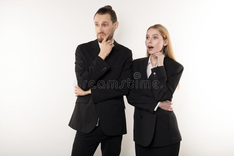Två affärspartners i svarta dräkter, stilig skäggig man och härlig blond kvinna tänka om lösning arkivbild