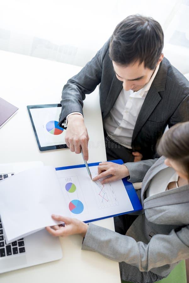 Två affärspartners som analyserar en rapport arkivbilder