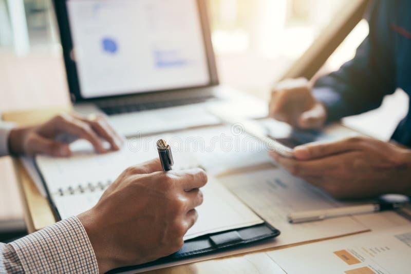Två affärspartnerskapcoworkers som i regeringsställning diskuterar finansiellt en graf för planera, och företag under ett rum för arkivfoto