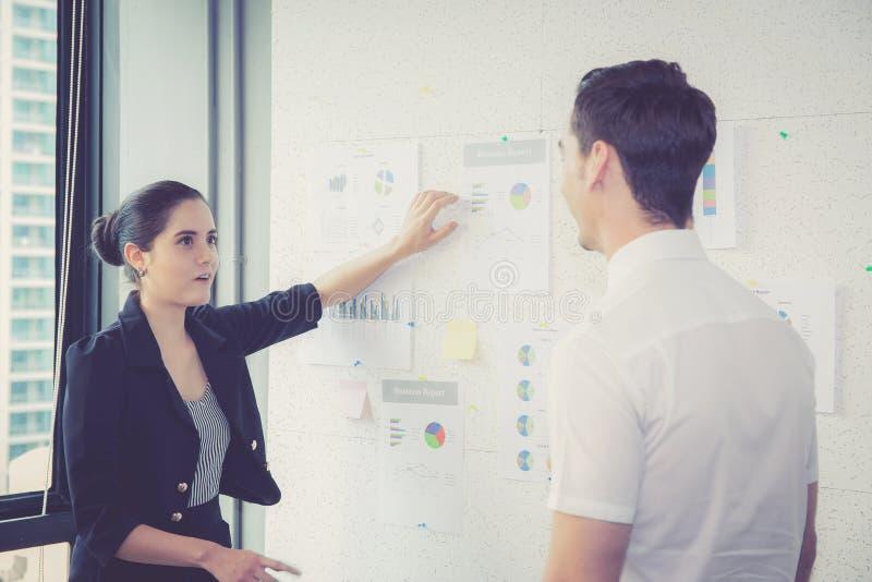 Två affärspersoner i det moderna kontoret som ser rapporten och analyserar med samtal i mötesrum royaltyfri fotografi
