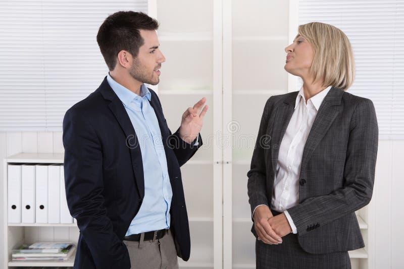 Två affärspersoner som arbetar i ett lag som tillsammans talar i av arkivbilder