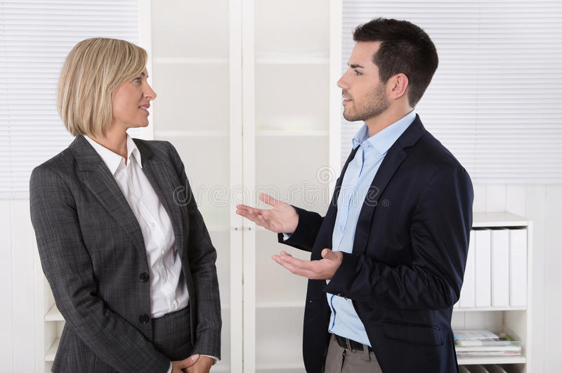 Två affärspersoner som arbetar i ett lag som tillsammans talar i av royaltyfri fotografi