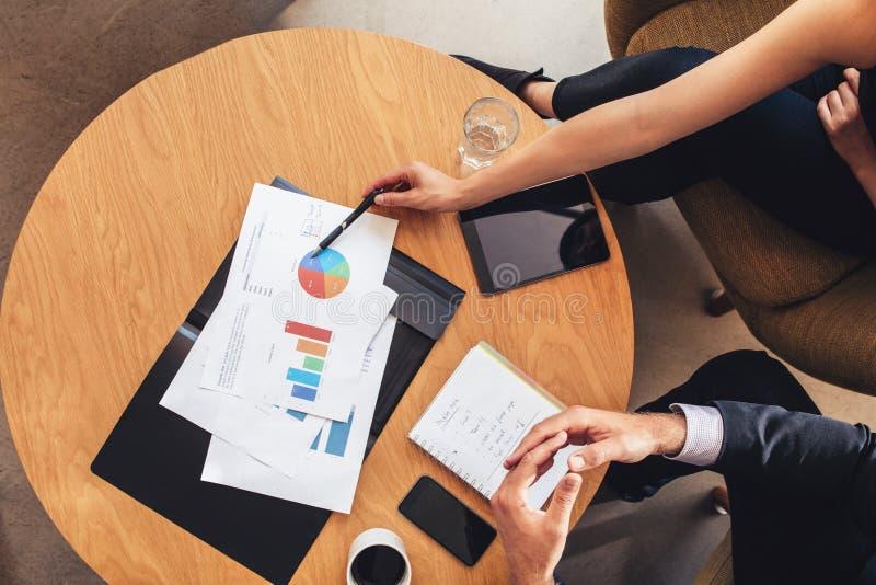 Två affärspersoner som arbetar med diagram runt om tabellen royaltyfria foton