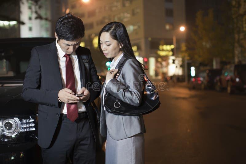 Två affärspersoner som ser mobiltelefonen arkivbild