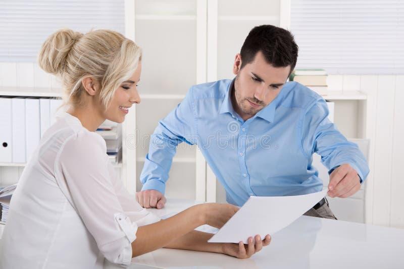 Två affärspersoner som sitter i kontoret som arbetar i ett lag, ser arkivbild