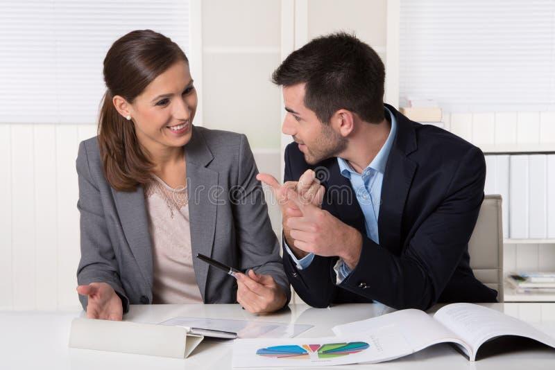 Två affärspersoner som sitter i kontoret som talar och analyserar arkivbild