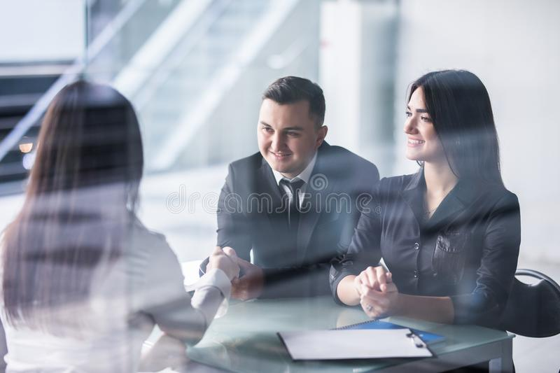 Två affärspersoner som skakar händer på ett avtal med fokusen till ett ungt par som placeras på ett skrivbord med mannen som ler  royaltyfria foton