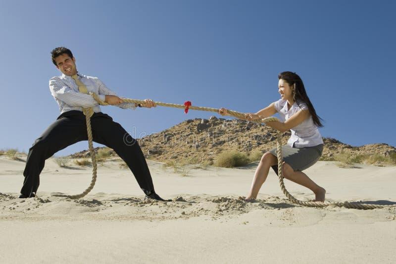 Två affärspersoner som spelar den Tug Of War In The öknen royaltyfri foto