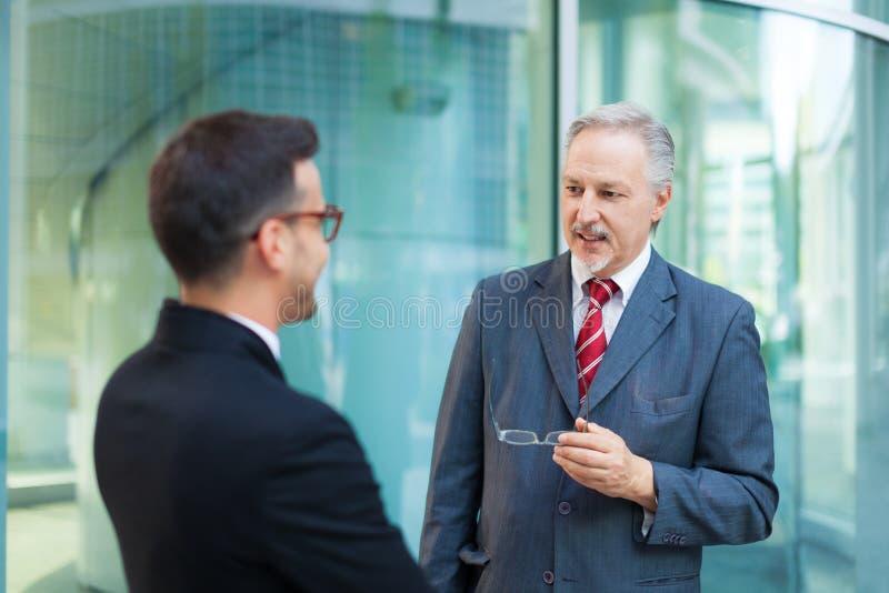 Två affärspersoner som tillsammans talar arkivbilder