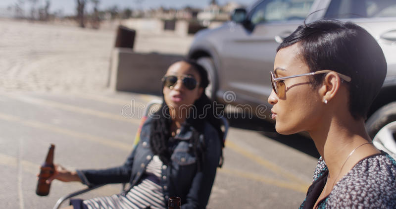 Två afrikansk amerikankvinnor som sitter i strandstolar som har en drin fotografering för bildbyråer