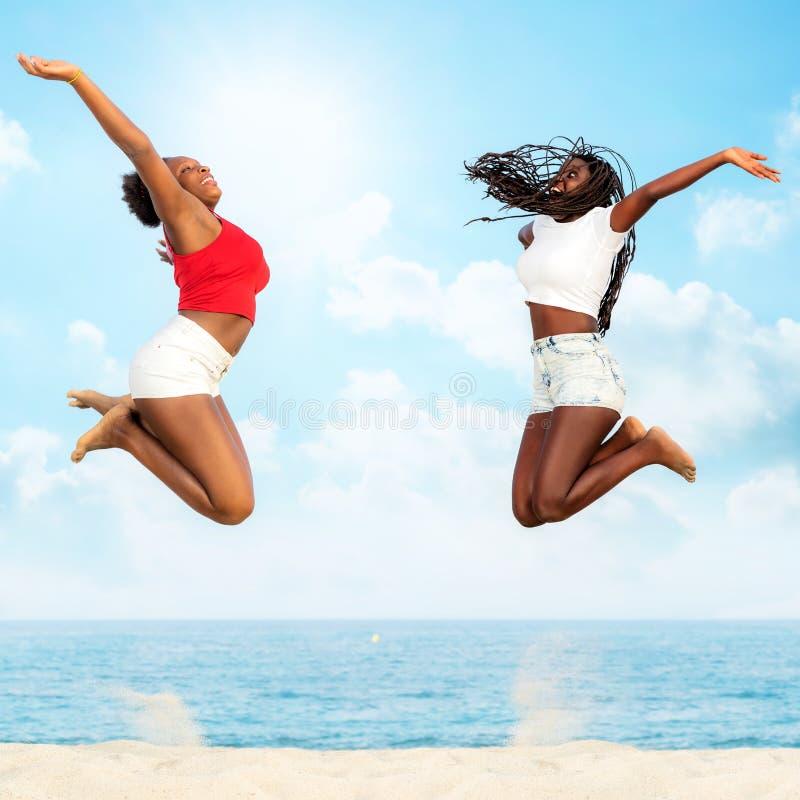 Två afrikanska vänner som tillsammans hoppar på stranden royaltyfri fotografi