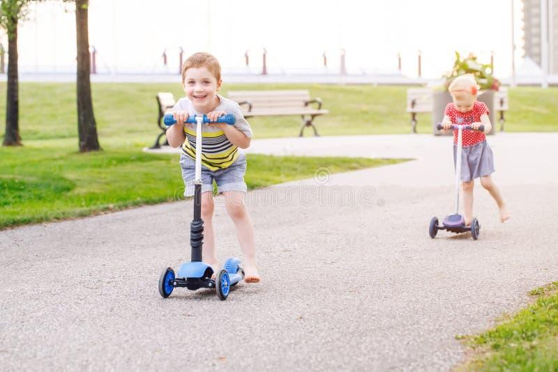 Två aktiva vänner flickan och pojken som för små barn rider sparkcyklar på vägen parkerar in, utomhus royaltyfri bild