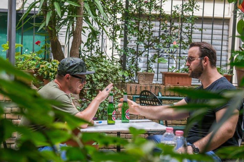Två albanian maffiagrabbar röker och dricker royaltyfria bilder
