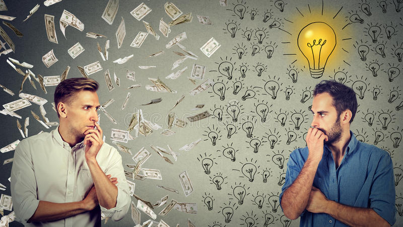 Två allvarliga affärsmän som ser de en under pengarregn annat med ljusa idéer royaltyfria foton