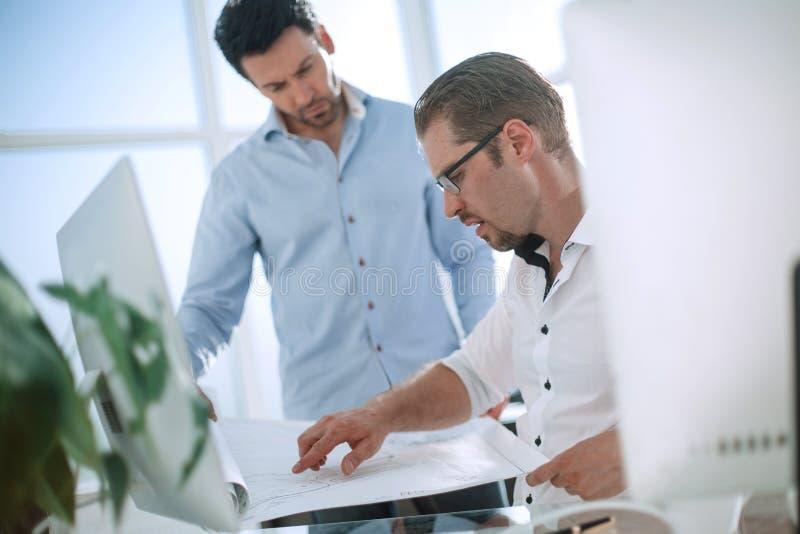 Två allvarliga affärsmän som talar och arbetar i kontoret royaltyfria bilder