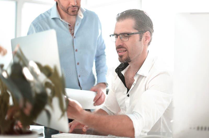 Två allvarliga affärsmän som talar och arbetar i kontoret arkivfoton