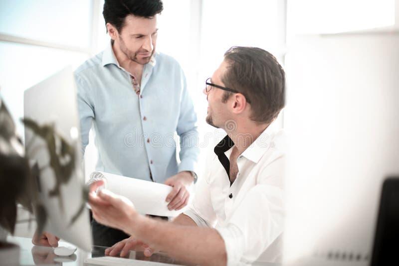 Två allvarliga affärsmän som talar och arbetar i kontoret fotografering för bildbyråer
