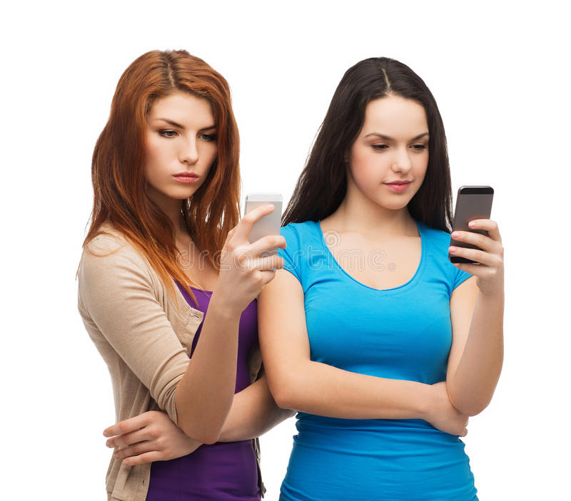 Två allvarliga tonåringar med smartphones royaltyfria bilder